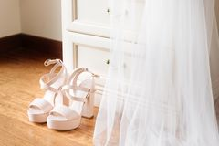Bridal pink shoes standing in front of the nightstand. Bridal veil falling down from the nightstand. Bridal morning concept in pastel colors royalty free stock images