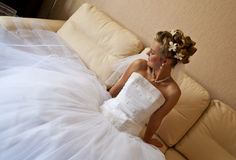 Bridal portrait. Young bride sitting on sofa in snow white dress, with modern hair style - looking to sideward Stock Photos