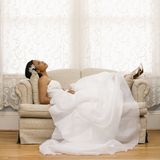 Bridal portrait. African-American bride lying on love seat Royalty Free Stock Photo