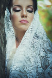 Bridal portrait of beautiful blue eyes woman with lace veil outd. Oor shot Royalty Free Stock Image