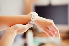 Bridal preparation, bride putting on jewelry Stock Images