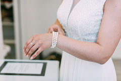 Bridal preparation, bride putting on jewelry Royalty Free Stock Photos