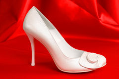 Bridal Shoe. White bridal shoe on a red background Stock Photos