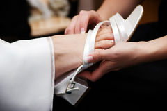 Bridal shoe. Maid of honour helping her bride put on her shoe Stock Image