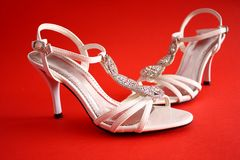 Bridal shoes. White open bridal bejewelled sandals with heels on red background Royalty Free Stock Photos