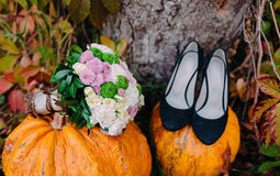 Bridal shoes and bouquet with autumn pumpkins. Wedding decorations. Close-up Stock Image