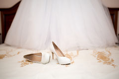 Bridal shoes and dress Stock Photos