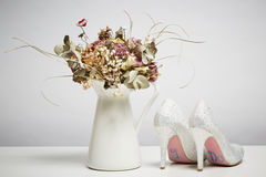 Bridal shoes and dried flowers in vase. On white table top Royalty Free Stock Images