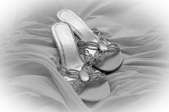 Bridal Shoes with Gown. Bride's shoes placed on her gathered satin white gown Stock Photo