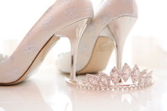 Bridal shoes and tiara. White cream and silver bridal shoes with silver metal heels accompanied by a silver and diamonte crystal tiara Royalty Free Stock Photos