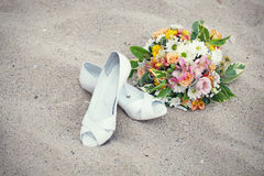 Bridal shoes and wedding bouquet Stock Photography