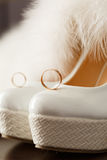 Bridal shoes with wedding rings and fur. Royalty Free Stock Photo