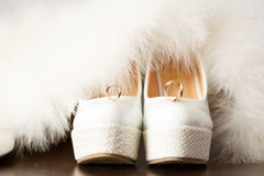 Bridal shoes with wedding rings and fur. Royalty Free Stock Image