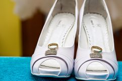 Bridal shoes and wedding rings stock images