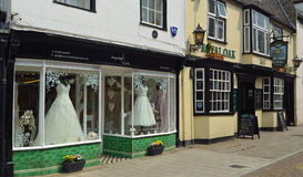 Bridal Shop Window with dresses on show next to public house. Royalty Free Stock Image