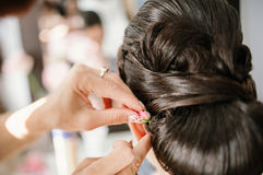 Bridal stylist attaching flower to bride coiffure Royalty Free Stock Image
