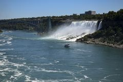 BRIDAL VEIL FALLS NIAGARA FALLS. Bridal Veil Falls can be seen from the Canadian side as a boat takes tourists out. Niagara Falls , New York can be seen in the stock photography