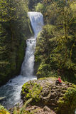Bridal veil falls, Oregon. Attractive woman sitting in on a rock with bridal veil falls on the side, Oregon USA Stock Image