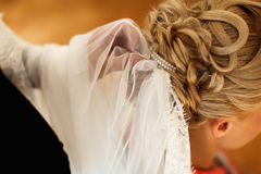 Bridal veil is put on a lady's hair Royalty Free Stock Photos