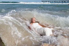 Bridal Washout. Bride lays on a rock on the beach as waves crash around her and carry her to the beach Stock Photos