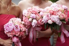 Bridal wedding flowers and bouquets. Three brides maid bouquets in shades of red and pink Stock Photo