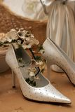 Bridal wedding shoes. Pair of bridal wedding shoes decorated with flowers, satin dress in background Stock Photos