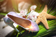 Bridal wedding shoes with diamante near the starfish, white flowers Royalty Free Stock Photo