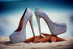 Bridal wedding shoes with diamante on starfish over beach background Royalty Free Stock Image