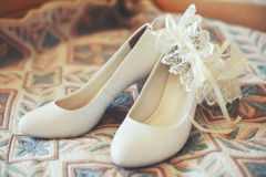 Bridal wedding shoes with garter on sofa, vintage toned. Bridal white wedding shoes with garter on sofa, vintage toned. Marriage concept Royalty Free Stock Images