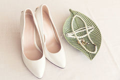Bridal wedding shoes and pearl jewelry on the table Royalty Free Stock Image