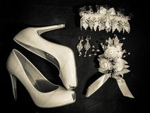 Bridal white shoes. Wedding shoes. Wedding garter. Wedding boutonniere. Garter of the bride. Black and white photo Stock Photo