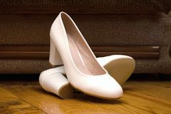 Bridal white shoes. Wedding shoes. Wedding garter. Shoes on the floor. Shoes at the sofa Stock Images