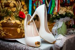 Bridal white shoes. Wedding shoes. Wedding garter. Shoes on the floor. Shoes at the sofa Royalty Free Stock Images