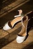 Bridal white shoes on a wooden background Stock Images