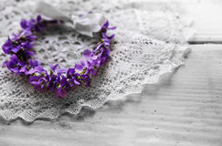 Bridal wreath lying on a lace napkin. Invitation card. Violet flowers. Royalty Free Stock Photos