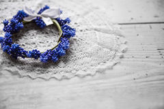 Bridal wreath lying on a lace napkin. Wedding accessories. Blue flowers. Stock Photos