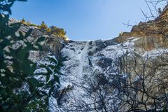 Bridalveil waterfall at Yosemite Park. Bridalveil waterfall from bellow and through the surrounding vegetation and tree leafs; the water around the waterfall Stock Images