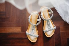Wedding shoes and the part of the wedding dress in foreground. The bride's shoes on the dark brown wooden floor with the part of the wedding dress in Royalty Free Stock Photography