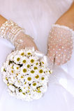 Bride 1. Camomiles flowers bridal nosegay in bride hands white dress royalty free stock photo
