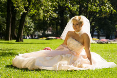 Bride. Smiling young bride sitting on a grass Royalty Free Stock Images