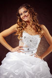 Bride. Fashion model wearing wedding dress at brown studio background Royalty Free Stock Photos