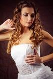 Bride. Fashion model wearing wedding dress at brown studio background Stock Photo