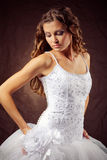 Bride. Fashion model wearing wedding dress at brown studio background Royalty Free Stock Photography