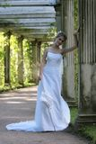 The bride. With an umbrella at an ancient column in park Stock Photo
