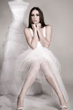 The bride. Before the wedding, sitting thoughtful beside the torso with the wedding dress royalty free stock photos