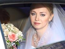Bride. Beautiful young bride into car. Wedding Stock Image
