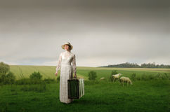 Bride. Portrait of a woman in white dress standing on a green meadow with an old suitcase in her hand Royalty Free Stock Photo