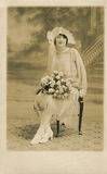Bride in the 1920s. A bride sits for her engagement/wedding portrait in the 1920s. She is seated, and is wearing a white dress, has a veil, and white roses are Stock Photos