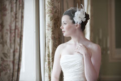 Bride. Pretty bride looking out of window and smiling on her wedding day Royalty Free Stock Photos