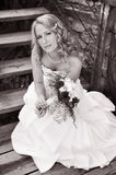 Bride. Beautiful young smiling bride with modern wedding hairstyle - long curly hairs on the stairs Stock Photos